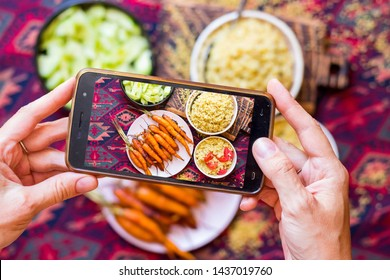 Phone screen food photo. Woman hands make food photography with smartphone. For blogging or social media use. Baked vegetables (carrots) with salad and bulgur. Healthy vegetarian, vegan food.
