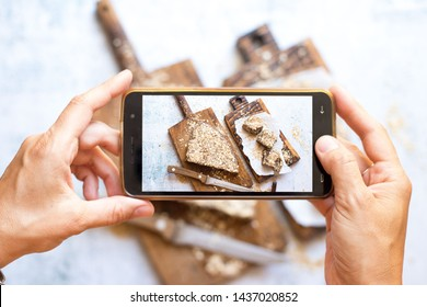 Phone screen food photo. Woman hands make food photography with smartphone. For blogging or social media use. Healthy vegetarian, vegan food. Sweet dessert cake on board and table.
