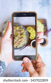Phone screen food photo. Woman hands make food photography with smartphone. For blogging or social media use. Healthy vegetarian, vegan food.  Asian eastern bulgur with vegetables.