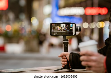 Phone with stabilizer, tripod, gimbal. Taking pictures and live video in New York city. Vlog, video blogging, street photography concept.