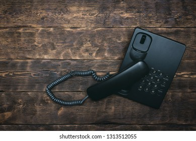 Phone with taken off handset on brown board background with copy space. Contact us.