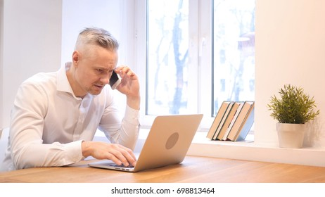 Phone Talk by Middle Age Man while Working on Laptop