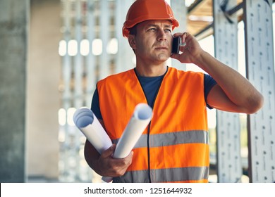 Phone talk. Thoughtful attentive builder in orange uniform standing with the drawings and having a phone talk