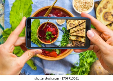 Phone vegan food photo of borscht - traditional Russian beetroot and cabbage vegetables soup. Create blog content photography with smartphone. Overhead, flat lay picture.