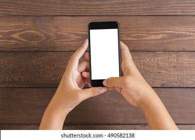 phone in woman hand showing white screen on wood table, mockup new phone style jet black color