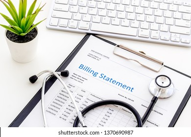 phonendoscope, billing statement and keyboard on work desk of doctor in hospital white background