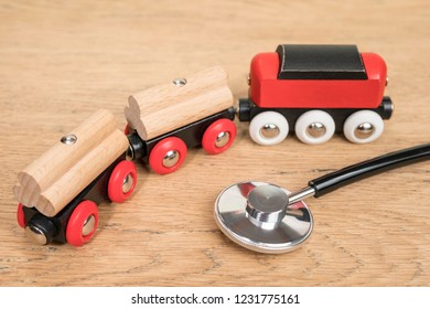 phonendoscope and toy train on the old wooden table