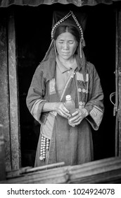 PHONGSALY, LAOS -  AUGUST, 2017 : Woman from the Akha tribe with traditional headgear standing outside house in  mountains in the north of Laos .