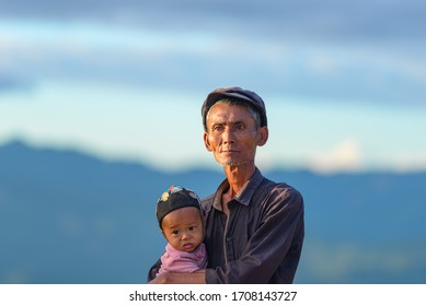 Phongsaly, Laos - november 2, 2019: portrait senior Akha man holding child wearing traditional hat belonging to minority ethnic group living in hilltribe villages around Phongsaly, North Laos.