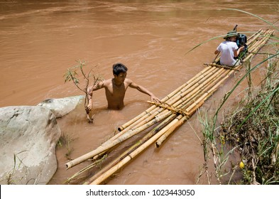 PHONGSALY PROVINCE,  LAOS - AUGUST 20, 2017:  A resident of the village helps in crossing the river using a bamboo raft while trekking in the mountains of northern Laos.