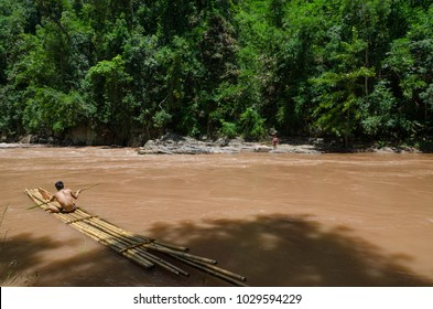 PHONGSALY PROVINCE,  LAOS - AUGUST 20, 2017:  A resident of the Akha village crossing the river using a bamboo raft  in the mountains of northern Laos.