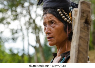 PHONGSALY PROVINCE,  LAOS - AUGUST 21, 2017:  Woman from the Akha tribe with traditional headgear posing outside house in mountains of North Laos.
