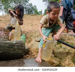 PHONGSALY PROVINCE,  LAOS - AUGUST 21, 2017:  Children from the Akha tribe taking a water from village well.