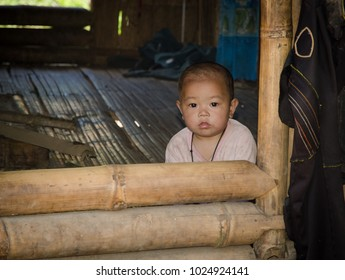 PHONGSALY PROVINCE,  LAOS - AUGUST 21, 2017:  Infant from the Akha tribe siting in a traditional house in mountains of Laos.
