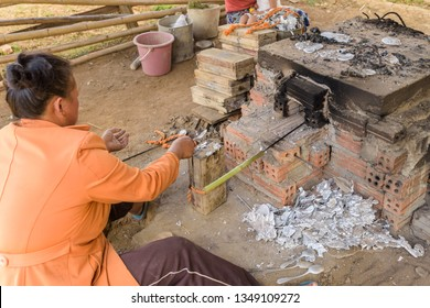 """PHONSOVAN, LAOS - JANUARY 29, 2019: A woman making """"war spoons"""" in Laos.  Locals make cutlery and jewellery using scrap aluminium salvaged from unexploded ordnance dropped during the U.S. secret war."""