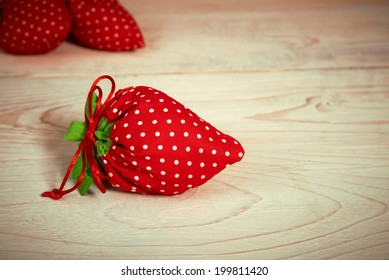 phony red strawberry on a wooden table
