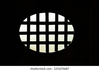 phot from the dark interior of an oval metal grid with the illuminated exterior