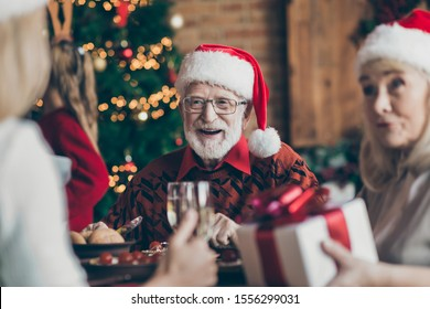 Phot of grandfather positive cheerful smiling in eye glasses spectacles wearing santa hat headwear feeling festive mood in conversation with guests