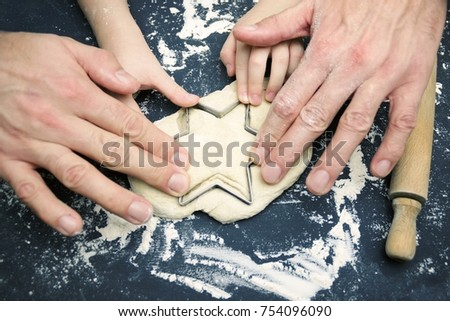 A photo from above of father and child hands cutting the star with a cookie cutter on the wooden table. An overhead photo of father's and kid's hands, flour, wheat dough, cookie cutter, rolling pin