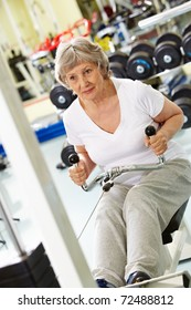 Photo of active woman pumping muscles on special equipment