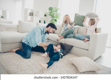 Photo of adopted family four members spend free time pillows fight giggle sit couch living room