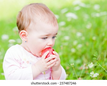 Photo of an adorable baby girl nibble an apple