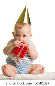 Photo of adorable baby holding birthday present and tasting it