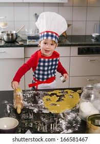 Photo of an adorable boy in a chef hat and apron making cookies in the kitchen.