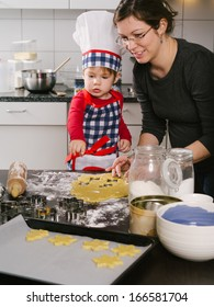 Photo of an adorable boy in a chef hat and apron and his mother making cookies in the kitchen.
