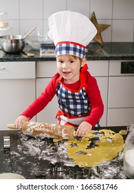 Photo of an adorable boy in a chef hat and apron using a rolling pin and making cookies in the kitchen.