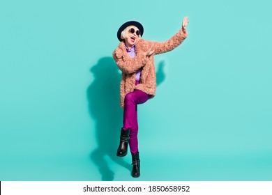 Photo of adorable cute old woman dressed vintage outerwear cap eyewear dancing isolated turquoise color background