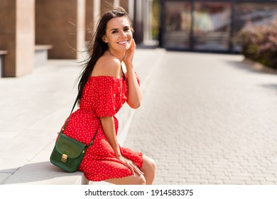 Photo of adorable sweet young lady wear red off-shoulders dress handbag sitting stairs outside urban city street
