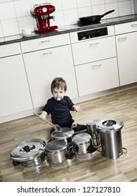 Photo of an adorable young boy using wooden spoons to bang pots and pans that are set up like a drumset. Desaturated and contrast increased.