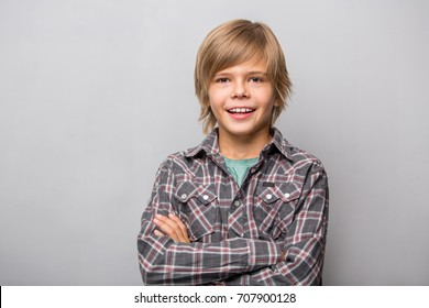 Photo of adorable young happy boy wearing shirt looking at camera over grey background