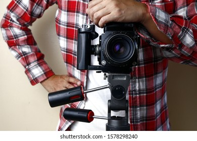 Photo of an adult man holding an old and vintage medium format film camera on a tripod.