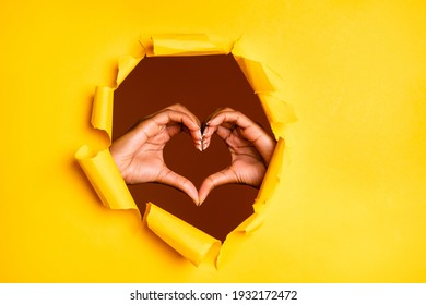 Photo of affectionate hands demonstrate love gesture heart shape through ripped yellow vibrant color background