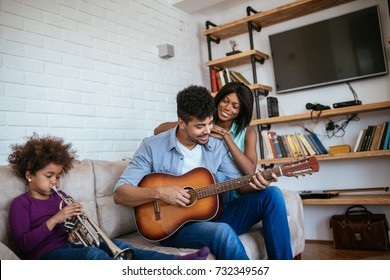 Photo of an african american family playing musical instruments at home.