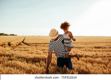 Photo of an african american father carrying his daughter in the wheat fields.