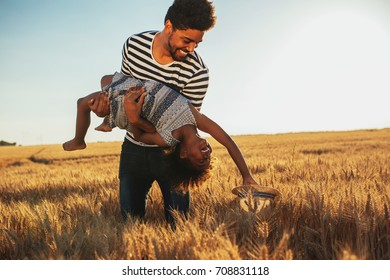 Photo of an african american father and daughter playing in the fields together.