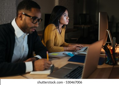 Photo of african businessman and woman working late at night in their office with laptop and computer.