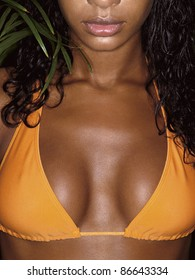 photo of african girl breasts in orange bikini with tropical plant behind