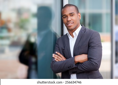 photo of african smiling businessman standing next to the glass wall