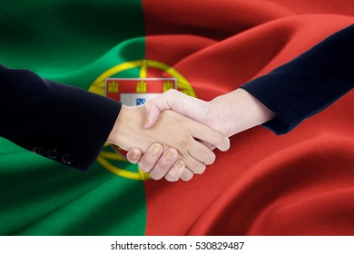 Photo of agreement handshake with two worker hands, shaking hands in front of a Portugal flag background