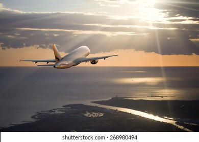Photo of the aircraft flying over the sea at sunset