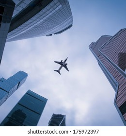 Photo of an airplane above the glass office buildings.