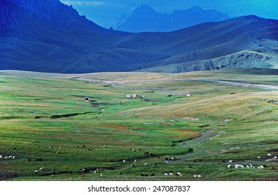 photo of Alay valley, Kyrgyzstan. In foreground steppe, and small sihouettes of grazing cattle, nomad's yurtas, in background mountains and clouds,  stylized and filtered to resemble an oil painting