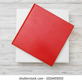 Photo album with a box on a wooden background. Red photo book with  leather cover. Photoalbum with a hard cover on a wooden background. Bright red photo album.