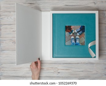 Photo album in a cardboard box. photobook with leather cover. photo book on a white background. open box with photo album.  photobook in a gift cardboard box