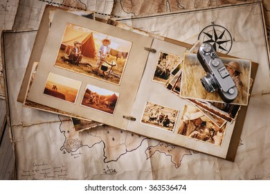 Photo album with photos of travel and vintage old camera on a background of old maps