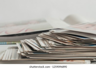 Photo album and pile of printed photographs on a white background.